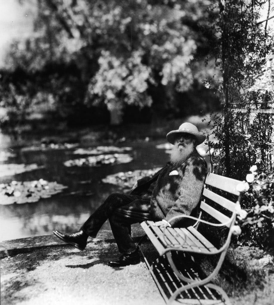 Claude Monet sitting on a bench beside the water lily pond in his garden at Giverny, 1910s, photo: Hulton Archive/Getty Images
