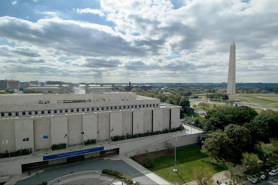 The Smithsonian's National Museum of American History, Kenneth E. Behring Center in Washington, D.C., with the Washington Monument and National Mall in the background.