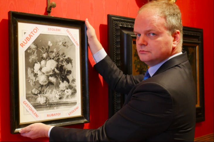 Uffizi director Eike Schmidt with a framed photograph of 'Vase of Flowers' and the word 'stolen' in Italian, English and German. Photo: @UffiziGalleries via Twitter