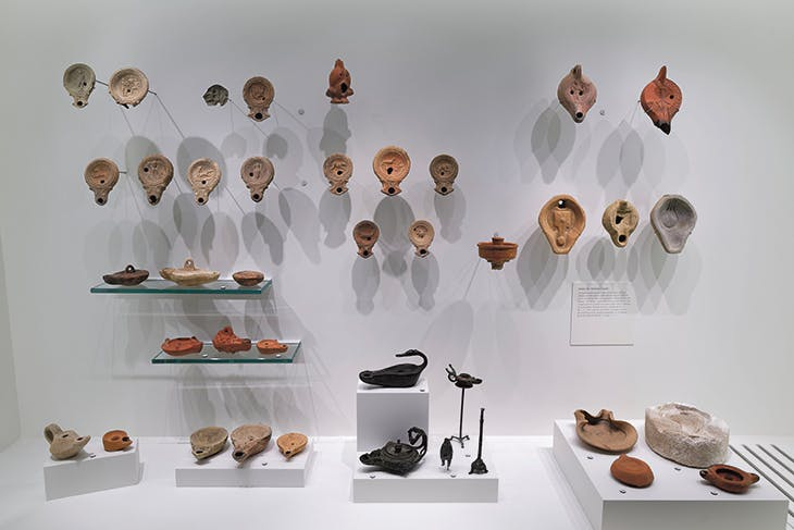 A display of decorated oil lamps – used for both everyday lighting and ritual practices – in terracotta and bronze, Roman era