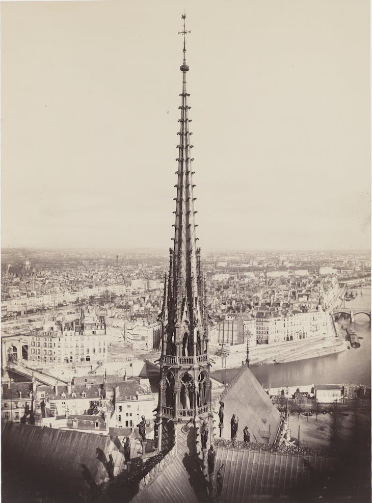 View of spire, roof with statuary, and cityscape beyond