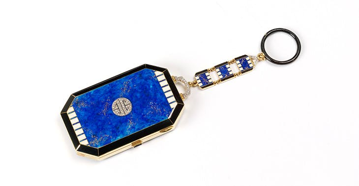 Gold vanity case decorated with blue, black and white enamel and diamonds, with a suspension chain with finger ring (1923–25), Lacloche, Paris.