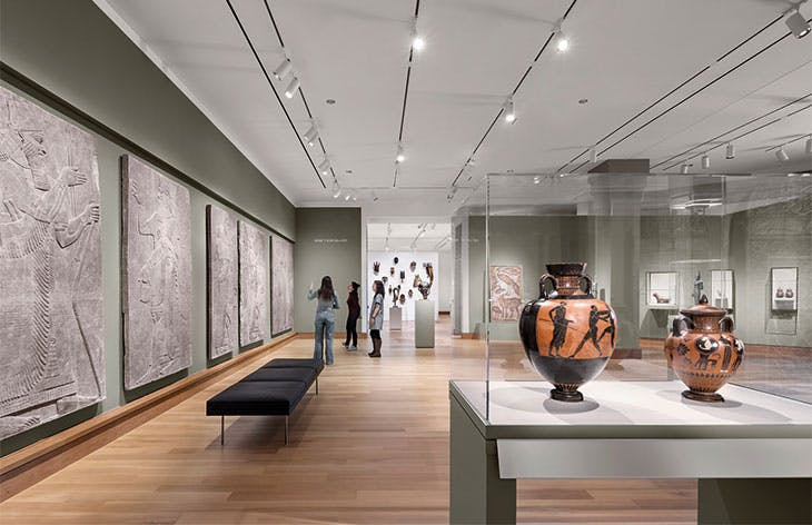 Ancient art in the newly renovated Kim Gallery includes, along the left-hand wall, reliefs from the north-west palace of Ashurnasirpal II at Nimrud, 883–859 BC. A display of traditional African art is visible in the Albright Gallery beyond.