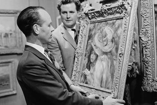 An art adviser, Graham Reid, examines a painting (Les Deux Soeurs) by Pierre-Auguste Renoir before its auction at Sotheby's in London in 1963.