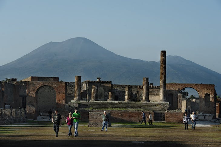 Tourists visit the archaeological site of Pompeii, with Vesuvius behind them