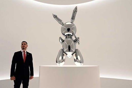 A security guard stands next to Jeff Koons' Rabbit (number two from an edition of three, plus one artist's proof; 1986) at Christie's New York in May 2019, ahead of its record-breaking sale at auction for $91.1m.