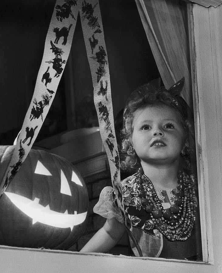 A girl waiting for guests to arrive at her Halloween party, USA (c. 1955), Joe Clark.