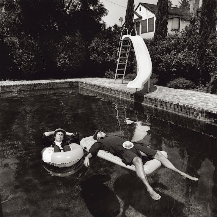 Peter Cook and Dudley Moore relaxing in a Beverly Hills swimming pool while in costume as the characters Pete and Dud, 1975.
