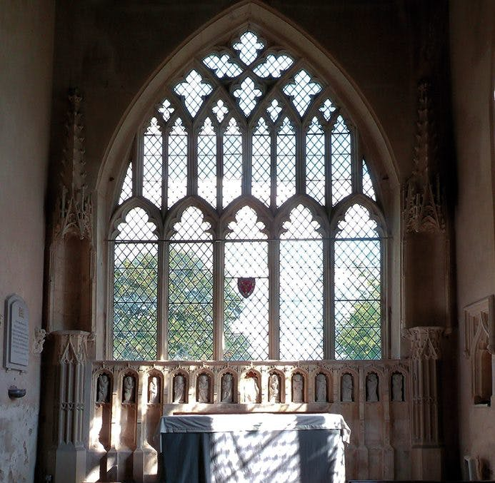 The east chancel wall, featuring a limestone reredos from the late 14th century, of the Parish Church of the Assumption of the Blessed Virgin Mary at Harlton, Cambridgeshire. Photo: © James Alexander Cameron