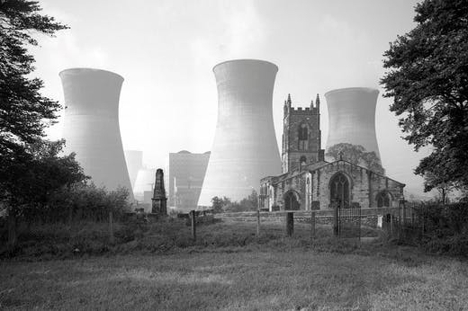 View of Ferrybridge B power station behind the Church of St Edward the Confessor in Brotherton, North Yorkshire, photographed by Eric de Maré in 1960. Photo: © Eric de Maré/RIBA collections