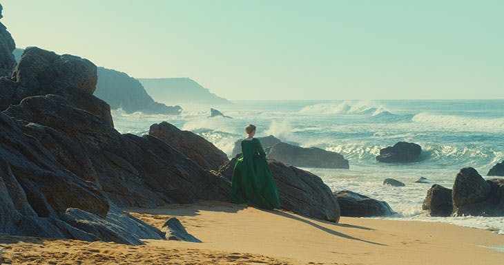 A woman in a green dress stands against a backdrop of rocks and waves.