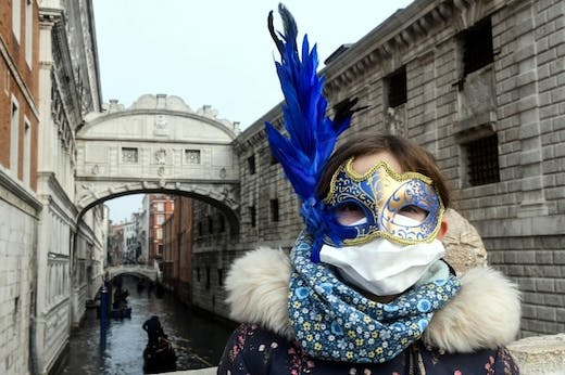 A tourist in Venice on 24 February 2020, wearing a protective face-mask and a Carnival mask.