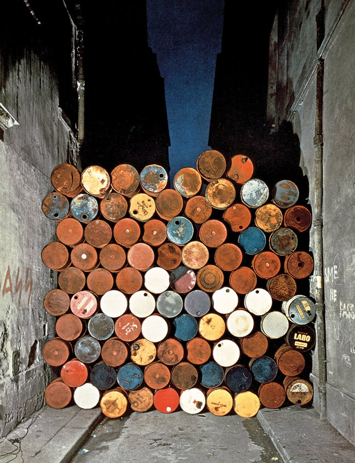 Installation view of Wall of Oil Barrels – The Iron Curtain in the Rue Visconti, Paris (1961–62), Christo and Jeanne-Claude.