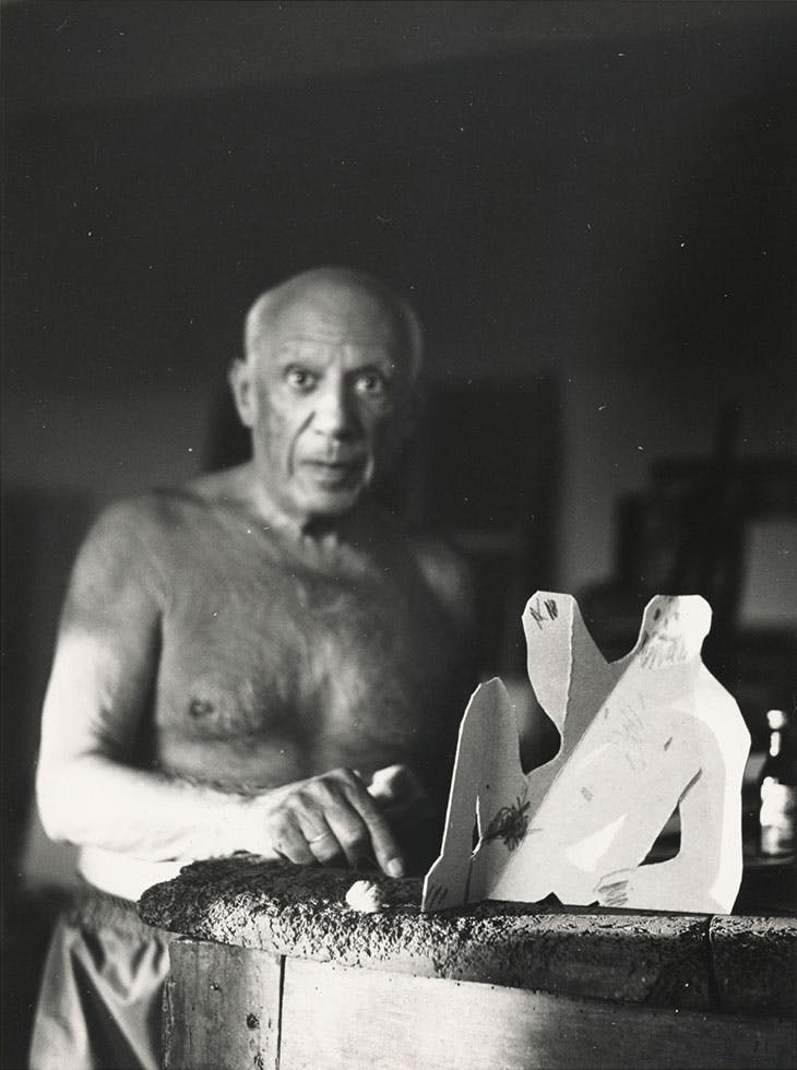 Picasso with a cardboard sculpture of a seated man for Le Déjeuner sur l'herbe, photographed in August 1962.