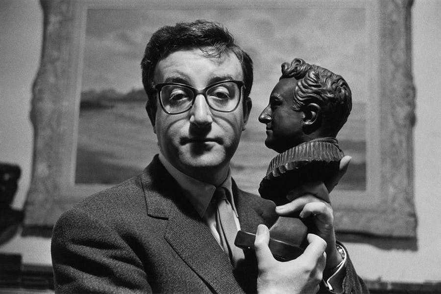 Peter Sellers holding a bust of himself.