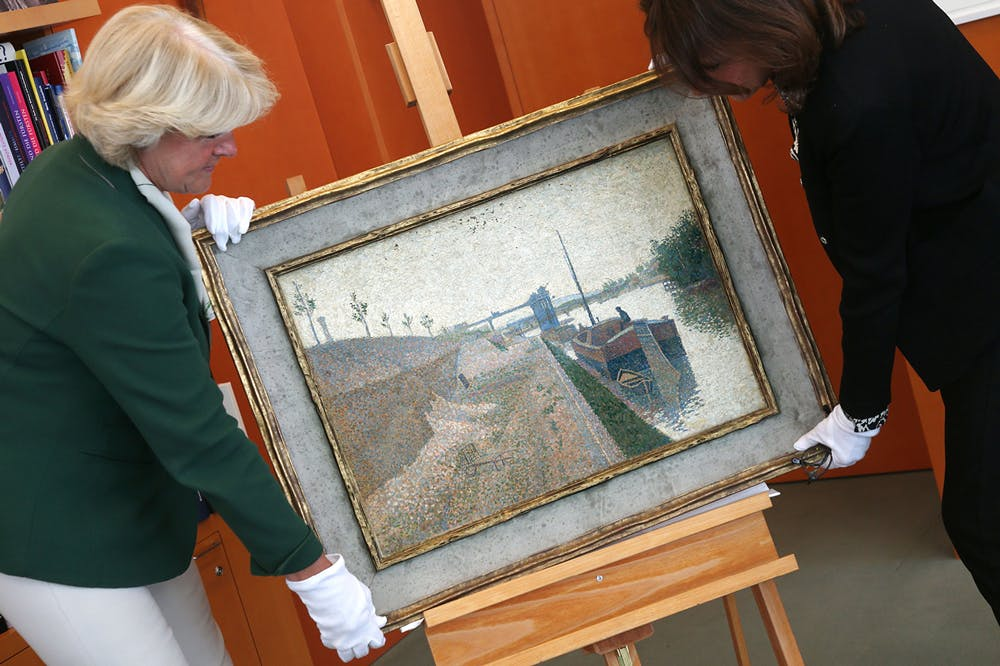 Monika Gruetters (left) hands over the painting 'Quai de Clichy' by Paul Signac to Agnes Sevestre-Barbe, representative of the heiress, as part of the return of art stolen under the Nazis and hoarded by Cornelius Gurlitt, the son of Nazi-era dealer Hildebrand Gurlitt in Berlin on July 3, 2019.