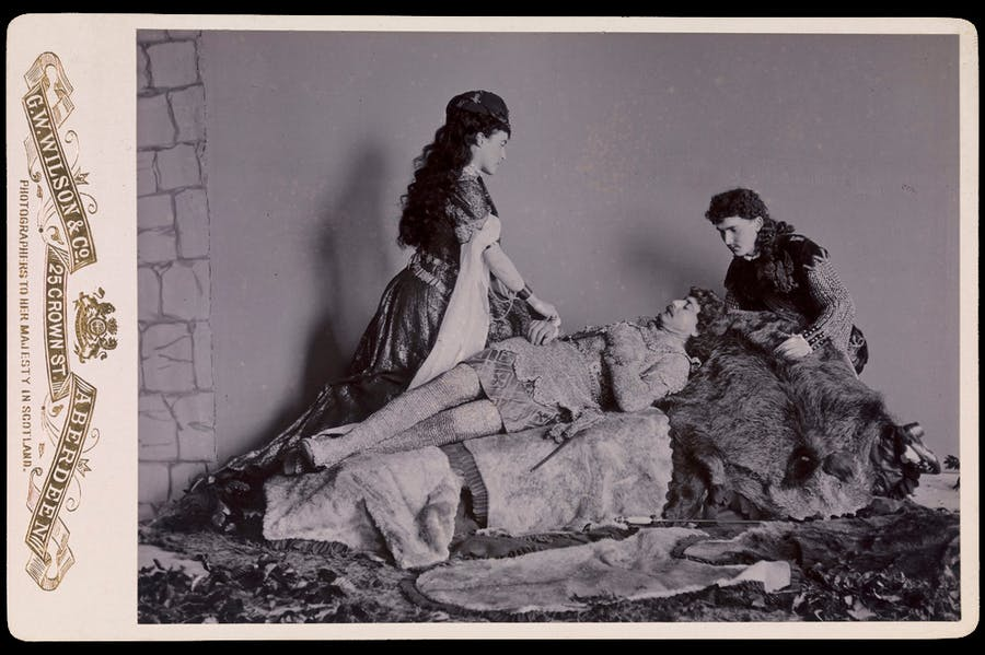 Photograph taken at Balmoral in 1893/94 by Charles Albert Wilson. Ethel Cadogan, Lord William Cecil and Dr Alexander Profeit re-enact a scene from Ivanhoe by Sir Walter Scott in which Rebecca and a page kneel over Ivanhoe. Royal Collection Trust/© HM Queen Elizabeth II 2020