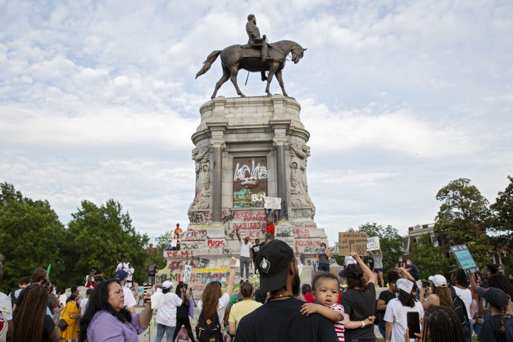 People gather around the Robert E. Lee statue on Monument Avenue in Richmond, Virginia, on June 4, 2020. Earlier, Virginia governor Ralph Northam announced plans to remove the statue of the Confederate general. Photo: Ryan M. Kelly/AFP via Getty Images