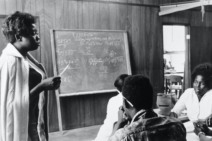 A volunteer mathematics teacher with students at Tufts, Mound Bayou, Mississippi (1968), Doris Derby.