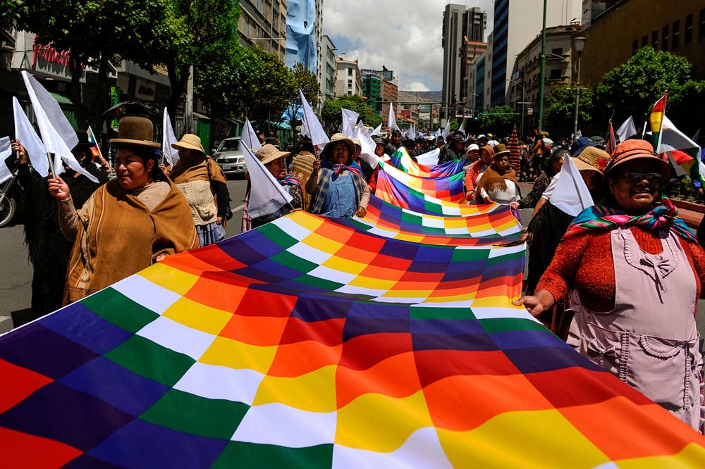 Demonstrators hold a Wiphala flag during a march called by students of the Universidad Mayor de San Andres and neighbourhood organisations march demanding peace in La Paz, on November 19, 2019. Photo by Jorge Bernal/AFP via Getty Images