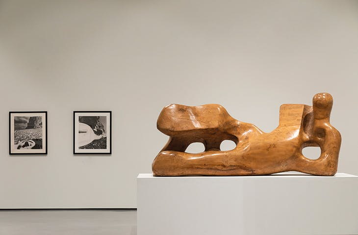 Installation view of Reclining Figure, 1936, Henry Moore (1898–1986) with prints from Perspective of Nudes (1961) by Bill Brandt at Hepworth Wakefield