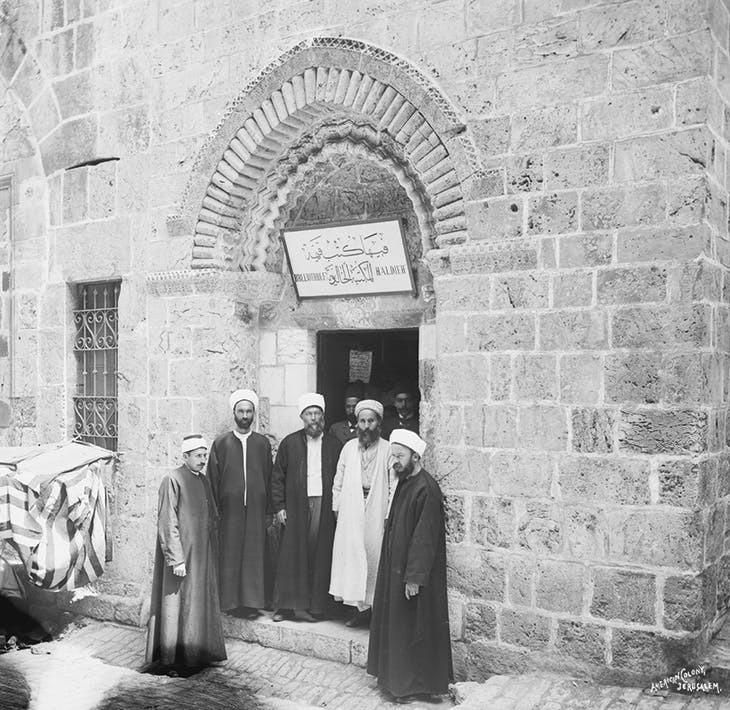 Members of the Khalidi family outside the newly opened library, (c. 1900), with (in white) Sheikh Taher al Jazaireh, founder of the Zahiriyya library in Damascus.