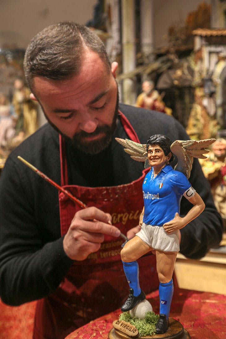 Gennaro Di Virgilio painting a statuette of Diego Maradona with wings on 26 November in Naples.