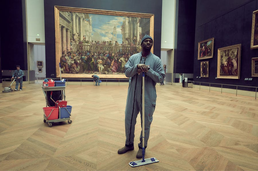 Omar Sy as Assane Diop in 'Lupin', with Veronese's 'Wedding Feast at Cana' in the background.