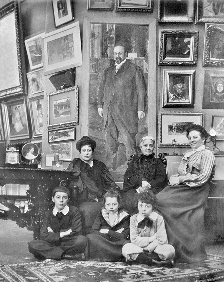 Margarita Morozov (far left) with her children and others in 1903, in front of the portrait of Mikhail Morozov by Valentin Serov (1902)