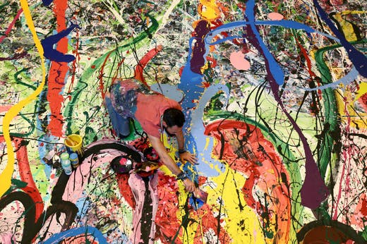 Art attack: Sacha Jafri painting his record- (and potentially back-) breaking artwork.