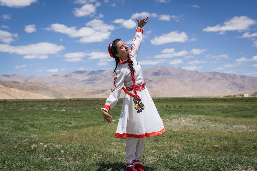 A girl in traditional Tajik dress dances at the opening of a new tourism centre in Bulunkul, Tajikistan (2019), Christopher Wilton-Steer.