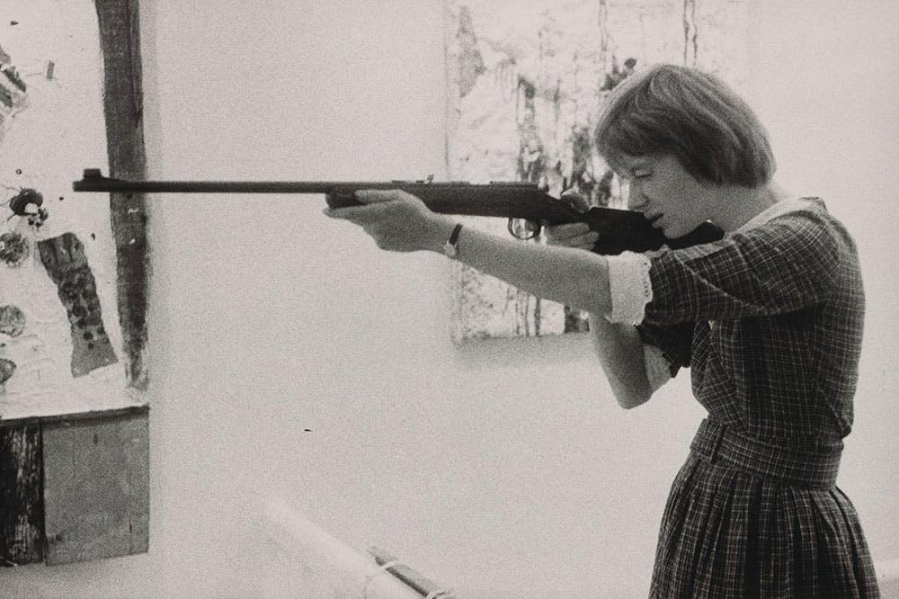 Niki de Saint-Phalle taking aim at her Feu à Volonté at Galerie J in Paris, in 1961.