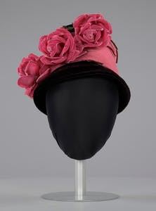 Black and pink beehive hat with pink flowers, (1941–1994), Mae's Milinery Shop. The Smithsonian National Museum of African American History and Culture