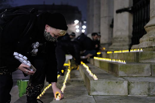 Carla Ecola, director of the Outside Project, lays memorial candles in Trafalgar Square as part of the Museum of Homelessness's 'Dying Homeless' project (Photo: Anthony Luvera)